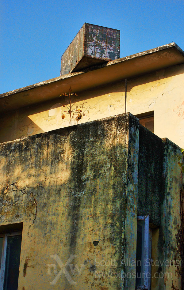 Crumbling house in India with box on roof